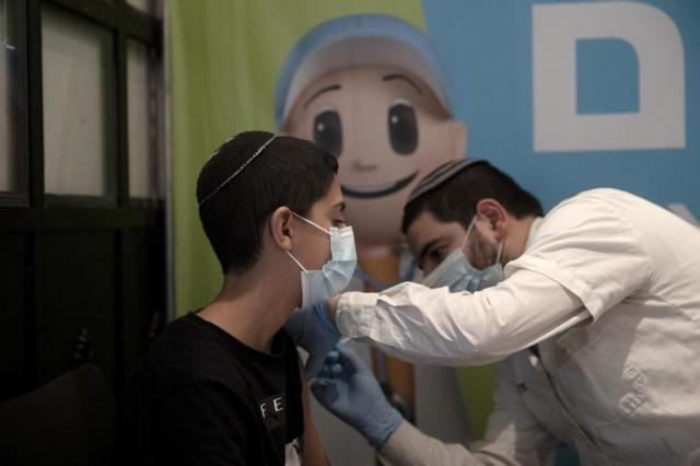 A 14-year-old Israeli receives a booster shot of the coronavirus vaccine at Clalit Health Service's center in the Cinema City complex in Jerusalem, Wednesday, Sept. 22, 2021. Israel is pressing ahead with its aggressive campaign offering coronavirus booster shots to almost anyone over 12, even after U.S. regulators called for limiting them to older patients or those at higher risk. (AP Photo/Maya Alleruzzo)