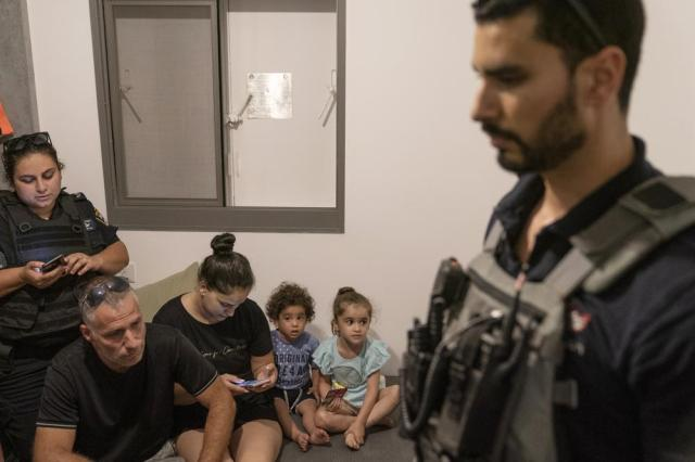 A family huddles in their home with bomb technicians and police as sirens warn of an incoming attack, Thursday, May 20, 2021, in Ashkelon, southern Israel. The family residence had just received a direct hit from an unexploded missile that landed on the top floor of their high rise apartment building. (AP Photo/John Minchillo)