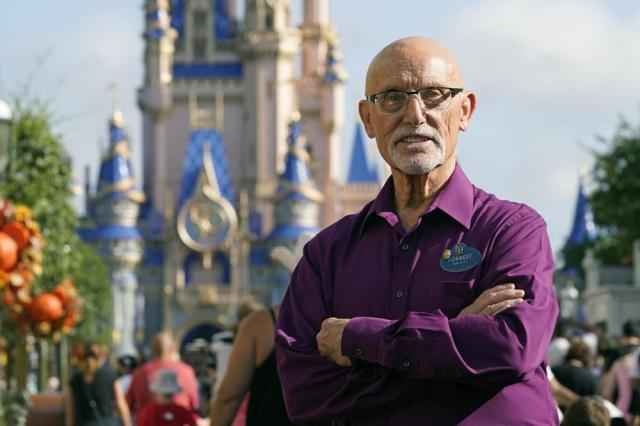 Forrest Bahruth stands on Main Street in front of the Cinderella Castle at the Magic Kingdom theme park at Walt Disney World Monday, Aug. 30, 2021, in Lake Buena Vista, Fla. Bahruth has been working at Disney since the opening day in 1971. (AP Photo/John Raoux)