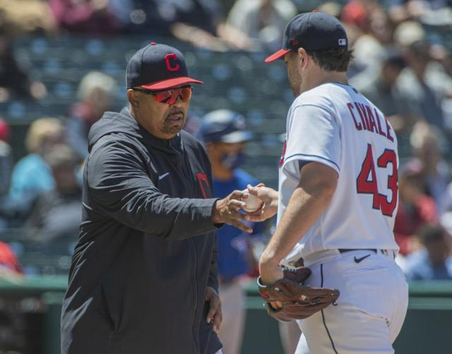Cleveland Indians bench coach De Mario Hale, left, takes the ball from Aaron Civale during the seventh inning of the first baseball game of a doubleheader against the Toronto Blue Jays in Cleveland, Sunday, May 30, 2021. Hale is filling in for Indians manager Terry Francona. (AP Photo/Phil Long)