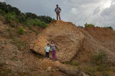 """Santos Portillo (50 años, arriba), Elvia Gutiérrez (46) y el hijo de ambos Jonathan Portillo (seis) posan para una foto en el sitio donde se encontraba su casa, que fue destruida por un derrumbe provocado por dos huracanes en La Reina, Honduras. Foto del 23 de junio del 2021. """"El patio era hermoso. Me divertía en una hamaca"""", dice Jonathan. """"Nadie va a poder vivir aquí"""", agrega su padre. (AP Photo/Rodrigo Abd)"""