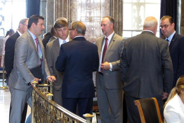 Louisiana state senators surround Senate President Page Cortez, R-Lafayette, third from the left, to talk through the remaining financial deals awaiting votes on the legislative session, Thursday, June 10, 2021, in Baton Rouge, La. (AP Photo/Melinda Deslatte)