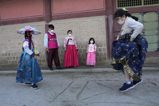 A girl wearing a face mask as a precaution against the coronavirus plays as she visits with her family members to celebrate Chuseok holidays, the Korean version of Thanksgiving Day, at the Gyeongbok Palace in Seoul, South Korea, Wednesday, Sept. 22, 2021. (AP Photo/Ahn Young-joon)