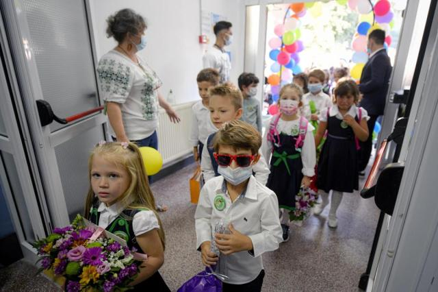 Children wearing face masks enter a school at the end of festivities marking the beginning of the school year, in Bucharest, Romania, Monday, Sept. 13, 2021. Children returned to classrooms in Romania, a country with one of the lowest COVID-19 vaccination rates in the European Union, as the daily infection numbers continue to rise. AP Photo/Andreea Alexandru)