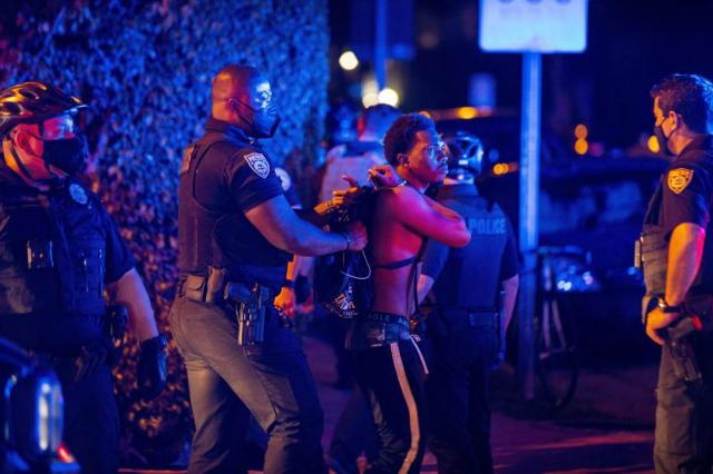 A person is arrested while out a few hours past curfew in Miami Beach, Fla., on Sunday, March 21, 2021. Miami Beach commissioners voted unanimously Sunday to extend the 8 p.m. to 6 a.m. curfew Thursday through Sunday in the South Beach entertainment district until at least April 12. (Daniel A. Varela/Miami Herald via AP)