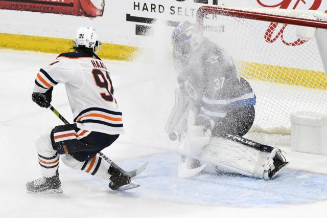 Winnipeg Jets goaltender Connor Hellebuyck (37) makes a save on Edmonton Oilers' Gaetan Haas (91) during second overtime period of an NHL hockey Stanley Cup playoff game, Monday, May 24, 2021, in Winnipeg, Manitoba. (Fred Greenslade/The Canadian Press via AP)