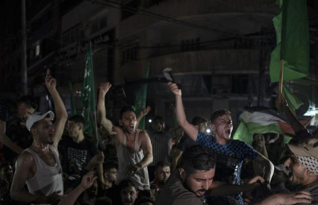 Palestinians chant slogans celebrating the cease-fire reached after an 11-day war between Hamas and Israel, in Gaza City, Friday, May 21, 2021. (AP Photo/Khalil Hamra)