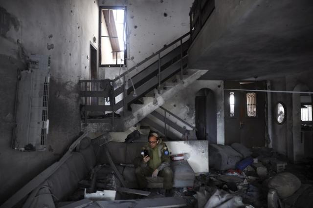 An Israeli soldier from the IDF Spokesperson's Unit inspects the damaged house after it was hit by a rocket fired from the Gaza Strip, In Ashkelon, Israel, Thursday, May 20, 2021. (AP Photo/Ariel Schalit)