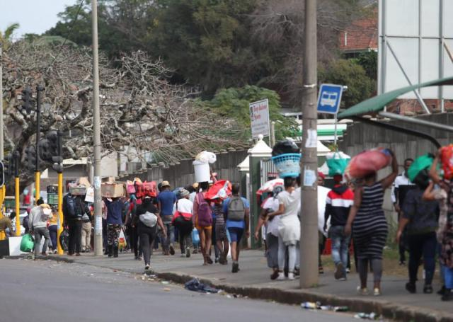 People make their way from a shopping mall carrying goods in Durban, South Africa, Tuesday July 13, 2021, as ongoing looting and violence continues. South Africa's rioting continued Tuesday with the death toll rising to 32 as police and the military struggle to quell the violence in Gauteng and KwaZulu-Natal provinces. (AP Photo)