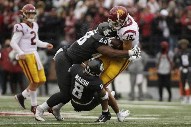 Washington State defensive lineman Amir Mujahid (48) and defensive back Armani Marsh (8) tackle Southern California wide receiver Drake London (15) during the first half of an NCAA college football game, Saturday, Sept. 18, 2021, in Pullman, Wash. (AP Photo/Young Kwak)