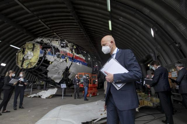 Presiding judge Hendrik Steenhuis and other trial judges and lawyers view the reconstructed wreckage of Malaysia Airlines Flight MH17, at the Gilze-Rijen military airbase, southern Netherlands, Wednesday, May 26, 2021. (AP Photo/Peter Dejong, Pool)