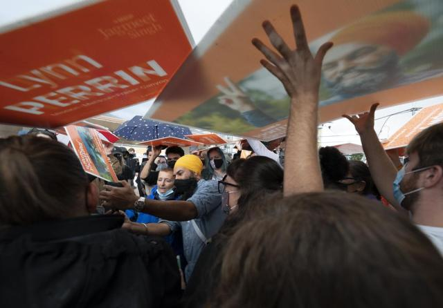 New Democratic Party supporters use signs as rain shields as NDP Leader Jagmeet Singh greets people during a campaign stop in Pitt Meadows, British Columbia, Sunday, Sept. 19, 2021. (Jonathan Hayward/The Canadian Press via AP)