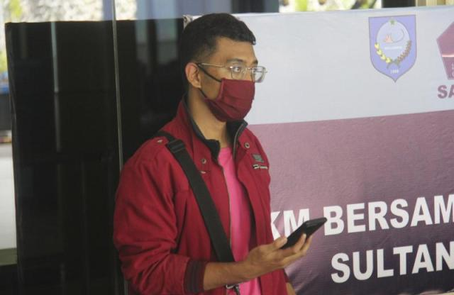 In this July 18, 2021, photo, a man who used a fake identity arrives at the Sultan Babullah airport in Ternate, Indonesia. The man with the coronavirus boarded a domestic flight disguised as his wife, wearing a niqab covering his face and carrying fake IDs and a negative PCR test result. He was arrested upon landing and tested positive for COVID-19. (AP Photo/Harmoko)