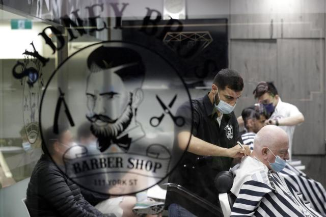 A barber shop clips and snips some of their first costumers in months after more than 100 days of lockdown to help contain the COVID-19 outbreak in Sydney, Monday, Oct. 11, 2021. (AP Photo/Rick Rycroft)