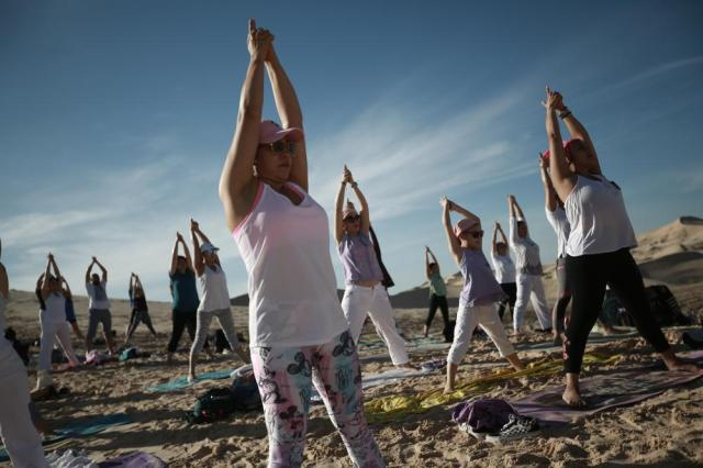 People hold a standing pose as they take part in the 6th annual Yoga Meeting in the Samalayuca Dunes, on the outskirts of Ciudad Juarez, Mexico, Saturday, July 3, 2021. This year yoga enthusiasts attended the outdoor event as a symbol of hope for those who survived the coronavirus and honoring those who have died from complications related to COVID-19. (AP Photo/Christian Chavez)
