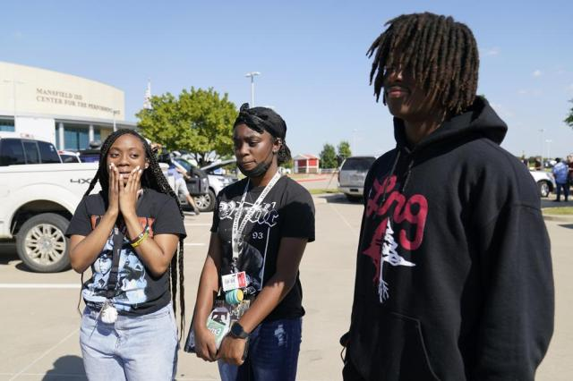 Timberview High School students Kayla Glaze, left, Hanyla Milligan, center and her brother Hamin Milligan right, respond a reporters questions outside the Mansfield ISD Center For The Performing Arts, Wednesday, Oct. 6, 2021 in Mansfield, Texas. Authorities say a student opened fire inside a Dallas-area high school during a fight, injuring four people before he fled. (AP Photo/Tony Gutierrez)