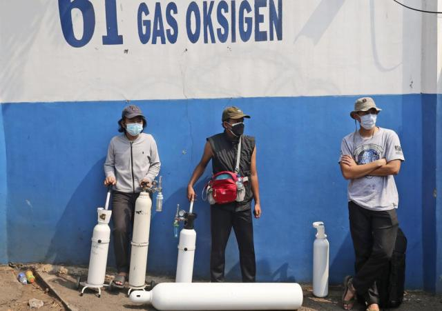 People wait for their turn to refill their oxygen tanks at a recharging station in Jakarta, Indonesia, Friday, July 9, 2021. The world's fourth most populous country is running out of oxygen as it endures a devastating wave of coronavirus cases and the government is seeking emergency supplies from other countries, including Singapore and China. (AP Photo/Tatan Syuflana)