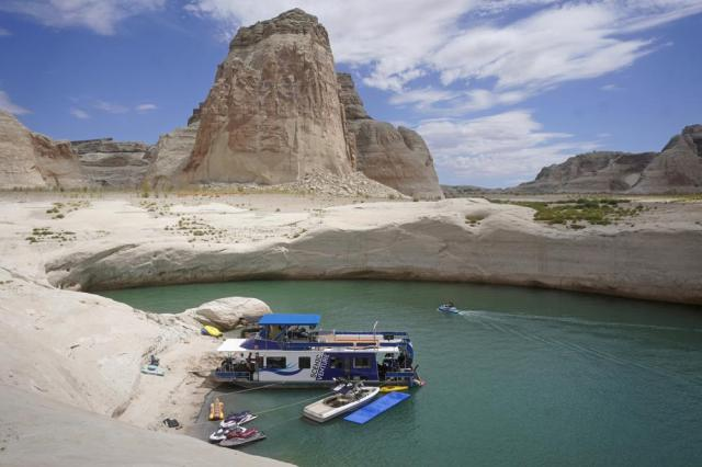 FILE - In this Friday, July 30, 2021 file photo, a houseboat rests in a cove at Lake Powell near Page, Ariz. This summer, the water levels hit a historic low amid a climate change-fueled megadrought engulfing the U.S. West.  Severe drought across the West drained reservoirs this year, slashing hydropower production and further stressing the region's power grids. And as extreme weather becomes more common with climate change, grid operators are adapting to swings in hydropower generation. (AP Photo/Rick Bowmer)