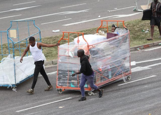People make their way with good on a trolley from a store in Durban, South Africa, Tuesday July 13, 2021, as ongoing looting and violence continues. South Africa's rioting continued Tuesday with the death toll rising to 32 as police and the military struggle to quell the violence in Gauteng and KwaZulu-Natal provinces. (AP Photo)