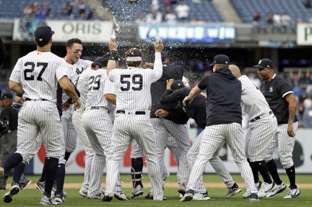 Teammates mob New York Yankees' Gary Sanchez after he hit a walkoff single against the Minnesota Twins during the 10th inning of a baseball game on Monday, Sept. 13, 2021, in New York. (AP Photo/Adam Hunger)
