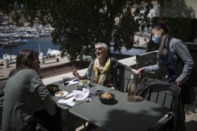FILE - In this May 19, 2021, file photo, Dany Barrau reacts with a waitress after being served, at a restaurant terrace in La Ciotat southern France. Coronavirus infections, hospitalizations and deaths are plummeting across much of Europe. Vaccination rates are accelerating, and with them, the promise of summer vacations. (AP Photo/Daniel Cole, File)