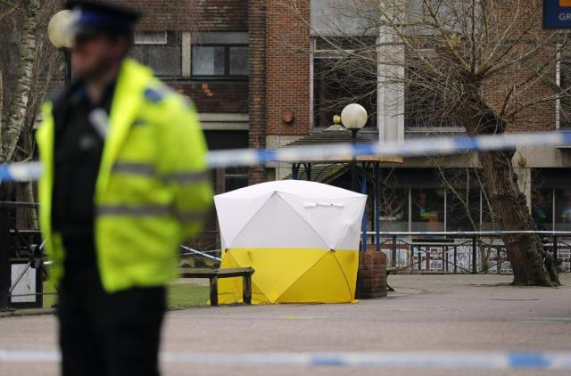 FILE - In this Tuesday, March 6, 2018 file photo, a police officer secures the area as a police tent covers the the spot in Salisbury, England. British police said Tuesday, Sept. 21, 2021 they are charging a third Russian suspect in the 2018 nerve agent attack on a former Russian agent in England. Scotland Yard said prosecutors believe there is sufficient evidence to charge a man known as Sergey Fedotov with conspiracy to murder, attempted murder, possessing and using a chemical weapon, and causing grievous bodily harm. (AP Photo/Frank Augstein, File)