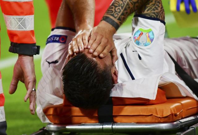 Italy's Leonardo Spinazzola covers his face after injuring during the Euro 2020 soccer championship quarterfinal match between Belgium and Italy at at the Allianz Arena in Munich, Germany, Friday, July 2, 2021. (AP Photo/Philipp Guelland, Pool Photo via AP)