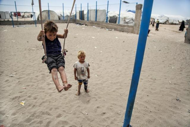 A boy plays on a swing at al-Hol camp, which houses families of members of the Islamic State group, in Hasakeh province, Syria, Saturday, May 1, 2021. It has been more than two years that some 27,000 children have been left to languish in al-Hol camp. Most of them not yet teenagers, they are spending their childhood in a limbo of miserable conditions with no schools, no place to play or develop and seemingly no international interest in resolving their situation. (AP Photo/Baderkhan Ahmad)
