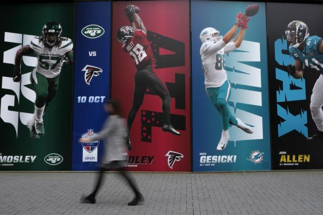A woman walks past posters advertising NFL at the Tottenham Hotspur Stadium in London, Thursday, Oct. 7, 2021. After a one-year hiatus due to the pandemic, the NFL returns to London on Sunday when the Atlanta Falcons play the New York Jets at Premier League club Tottenham's $1.6 billion facility (AP Photo/Kirsty Wigglesworth)