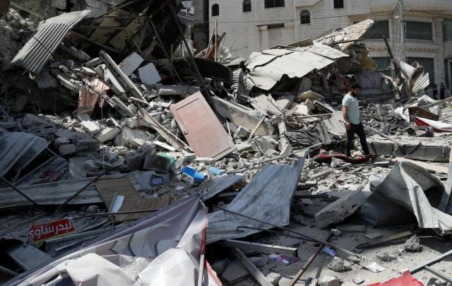 A man inspects the rubble of destroyed residential building which was hit by Israeli airstrikes, in Gaza City, Thursday, May 20, 2021. (AP Photo/Adel Hana)