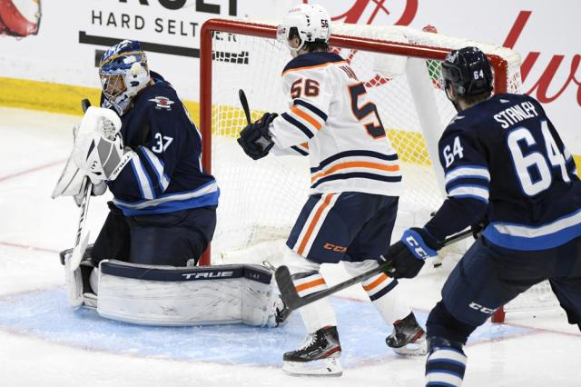 Winnipeg Jets goaltender Connor Hellebuyck (37) makes a save as Edmonton Oilers' Kailer Yamamoto (56) looks for the rebound during the third period of an NHL hockey Stanley Cup playoff game, Monday, May 24, 2021, in Winnipeg, Manitoba. (Fred Greenslade/The Canadian Press via AP)