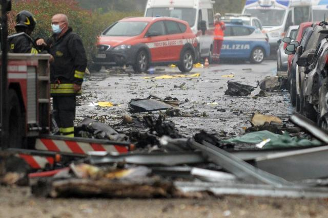 Firefighters work on the site of a plane crash, in San Donato Milanese suburb of Milan, Italy, Sunday, Oct. 3, 2021. According to media reports, a small plane carrying five passengers and the pilot crashed into an apparently vacant office building in a Milan suburb. (Claudio Furlan/LaPresse via AP)