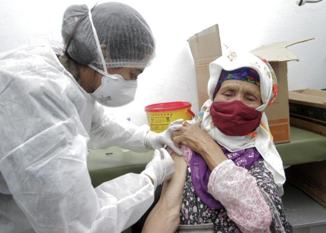 A soldier administrates the COVID-19 vaccine to a woman in Kesra,130 kilometers (80 miles) south of Tunis, Tuesday, July 13, 2021. As part of the efforts from the Tunisian government to try to stop the increasing number of infections in the country, the militaries were deployed to some cities and rural areas hardly affected by COVID-19 or with a very low rate of vaccination, to vaccinate people. (AP Photo/Saber Zidi)