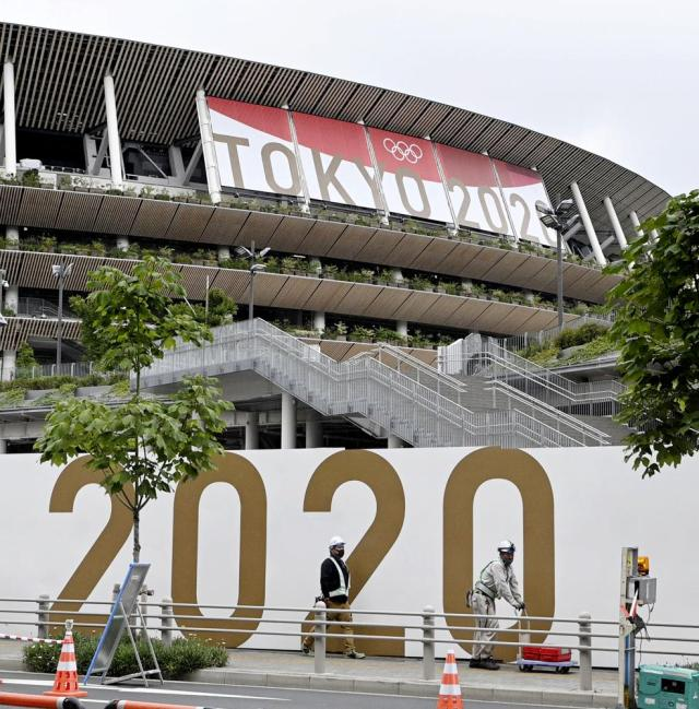 Workers wearing face masks walk past the National Stadium in Tokyo, Thursday, July 8, 2021. Japan is set to place Tokyo under a state of emergency that would last through the Olympics, fearing an ongoing COVID-19 surge will multiply during the Games. (Kyodo News via AP)
