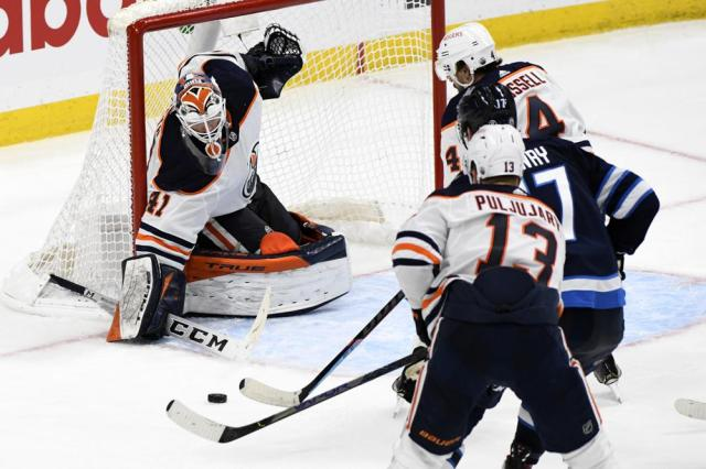 Edmonton Oilers goaltender Mike Smith (41) makes a save on Winnipeg Jets' Adam Lowry (17)during second overtime period of an NHL hockey Stanley Cup playoff game, Monday, May 24, 2021, in Winnipeg, Manitoba. (Fred Greenslade/The Canadian Press via AP)