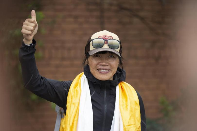 Tsang Yin-hung, 45, of Hong Kong who scaled Mount Everest from the base camp in 25 hours and 50 minutes, and became the fastest female climber gestures to media as she arrives in Kathmandu, Nepal, Sunday, May 30, 2021. The Hong Kong teacher and retired attorney from Chicago who became the oldest American to scale Mount Everest, on Sunday returned safely from the mountain where climbing teams have been struggling with bad weather and a coronavirus outbreak. (AP Photo/Bikram Rai)