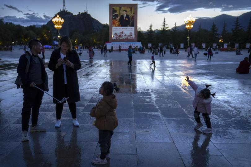 Tourists stand near a large mural depicting Chinese President Xi Jinping on a square near the Potala Palace in Lhasa in western China's Tibet Autonomous Region, Tuesday, June 1, 2021. Tourism is booming in Tibet as more Chinese travel in-country because of the coronavirus pandemic, posing risks to the region's fragile environment and historic sites. (AP Photo/Mark Schiefelbein)