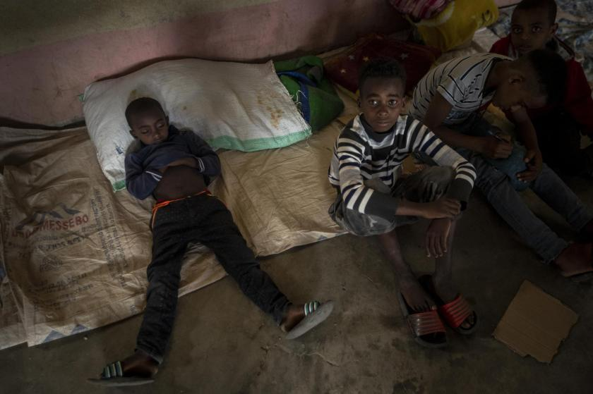 """An exhausted Tigrayan boy sleeps during the day at a camp for the internally-displaced in an elementary school in Mekele, in the Tigray region of northern Ethiopia Monday, May 10, 2021. For months, both Ethiopia and Eritrea denied the presence of Eritrean soldiers in Tigray but Ethiopia's Prime Minister Abiy Ahmed later acknowledged in March that Eritrean troops were """"causing damages to our people."""" (AP Photo/Ben Curtis)"""
