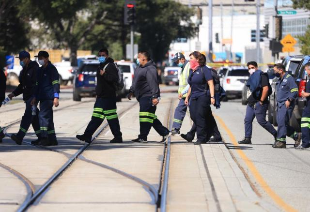Valley Transportation Authority workers cross Younger Avenue near the scene of a mass shooting in San Jose, Calif., on Wednesday, May 26. 2021. Gunfire erupted Wednesday at a railyard in San Jose, and a sheriff's spokesman said multiple people were killed and wounded and that the suspect was dead. (Randy Vazquez/Bay Area News Group via AP)
