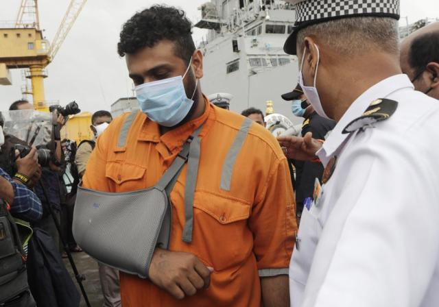 People rescued by the Indian navy from a barge that sank in the Arabian sea walk out from Indian naval ship INS Kochi in Mumbai, India, Wednesday, May 19, 2021. The barge carrying personnel deployed for offshore drilling sank off Mumbai as a deadly cyclone blew ashore this week. (AP Photo/Rajanish Kakade)