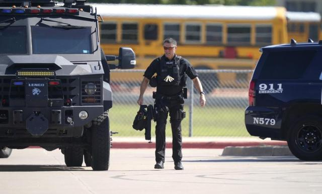 A law enforcement officer walks in the parking lot of Timberview High School after a shooting inside the school in south Arlington, Texas, Wednesday, Oct. 6, 2021. (AP Photo/LM Otero)