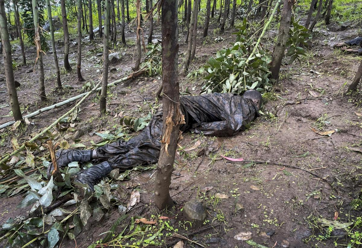 """The dead body of an unidentified man wearing a military uniform lies on the ground amongst trees near the village of Chenna Teklehaymanot, in the Amhara region of northern Ethiopia Thursday, Sept. 9, 2021. At the scene of one of the deadliest battles of Ethiopia's 10-month Tigray conflict, witness accounts reflected the blurring line between combatant and civilian after the federal government urged all capable citizens to stop Tigray forces """"once and for all."""" (AP Photo)"""