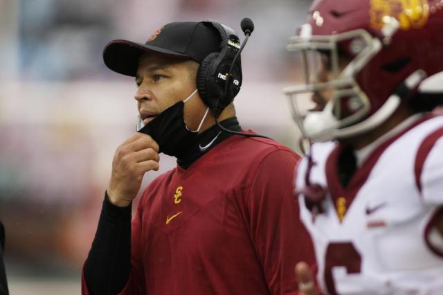 Southern California interim head coach Donte Williams, left, walks toward his team during a break in play in the first half of an NCAA college football game against Washington State, Saturday, Sept. 18, 2021, in Pullman, Wash. (AP Photo/Young Kwak)
