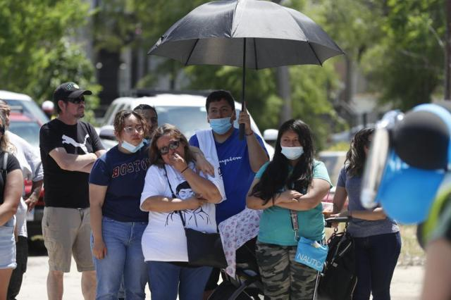 Mourners gather as they shed tears during a news conference announcing the opening of Adam's Place Inc., a not-for profit organization aiming to help at-risk youth from Chicago and other Midwestern cities to remain out of trouble, Wednesday, May 26, 2021 in Chicago's West Side. Adam Toledo, 13, was shot and killed March 29 by a Chicago police officer. (AP Photo/Shafkat Anowar)