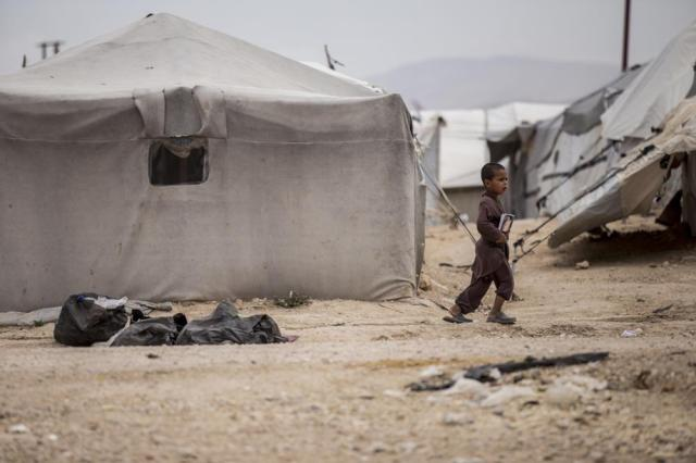 A boy holds a book as he walk at al-Hol camp, which houses families of members of the Islamic State group, in Hasakeh province, Syria, Saturday, May 1, 2021.   It has been more than two years that some 27,000 children have been left to languish in al-Hol camp, which houses families of IS members.   Most of them not yet teenagers, they are spending their childhood in a limbo of miserable conditions with no schools, no place to play or develop and seemingly no international interest in resolving their situation.  (AP Photo/Baderkhan Ahmad)