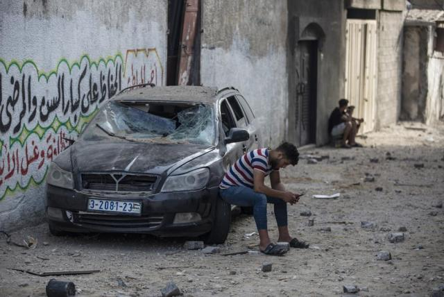 A Palestinian man sits on a damaged car following Israeli airstrikes on Jabaliya refugee camp, northern Gaza Strip, Thursday, May 20, 2021. Heavy airstrikes pummeled a street in the Jabaliya refugee camp in northern Gaza, destroying ramshackle homes with corrugated metal roofs nearby. The military said it struck two underground launchers in the camp used to fire rockets at Tel Aviv. (AP Photo/Khalil Hamra)