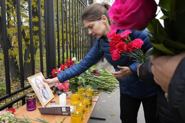 A woman puts a portrait of a victim of shooting next to flowers and candles outside the Perm State University following a campus shooting in Perm, about 1,100 kilometers (700 miles) east of Moscow, Russia, Tuesday, Sept. 21, 2021. A student opened fire at the university, leaving a number of people dead and injured, before being shot in a crossfire with police and detained. Beyond saying that he was a student, authorities offered no further information on his identity or a possible motive. (AP Photo/Dmitri Lovetsky)