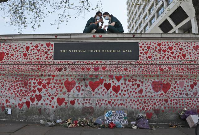 """FILE - In this Tuesday, April 27, 2021 file photo, nurses from the nearby St Thomas' hospital sit atop the National Covid Memorial Wall in London. British Prime Minister Boris Johnson will on Tuesday, Sept. 28 finally meet with members of the COVID-19 Bereaved Families for Justice campaigning group, who for more than a year have sharply criticized his handling of the coronavirus pandemic. Johnson's Downing Street office confirmed Monday that the prime minister will hold a """"private meeting"""" with members of the group. (AP Photo/Frank Augstein, file)"""