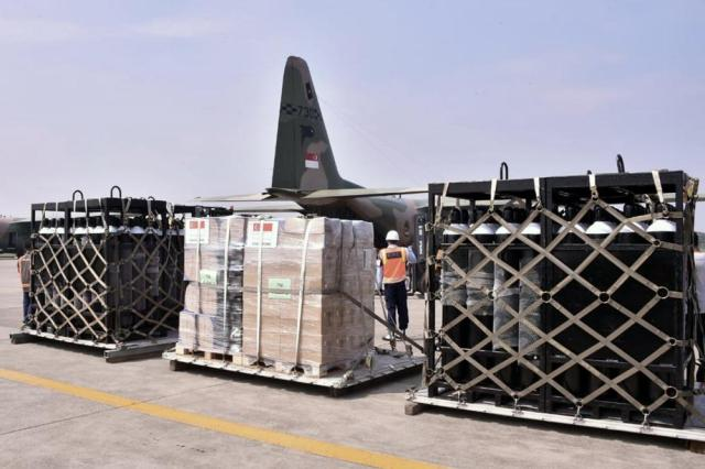 In this photo released by Indonesian Armed Forces, a military personnel stand guard near oxygen canisters and other relief goods unloaded from a Singaporean Air Force cargo plane at Halim Perdanakusuma Airbase in Jakarta, Indonesia, Friday, July 9, 2021. The world's fourth most populous country is running out of oxygen as it endures a devastating wave of coronavirus cases and the government is seeking emergency supplies from other countries, including Singapore and China. (Indonesian Armed Forces via AP)