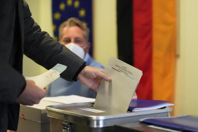A man casts his vote for Germany's national parliament election at a polling station in Berlin, Germany, Sunday, Sept. 26, 2021. German voters are choosing a new parliament in an election that will determine who succeeds Chancellor Angela Merkel after her 16 years at the helm of Europe's biggest economy. (AP Photo/Markus Schreiber)